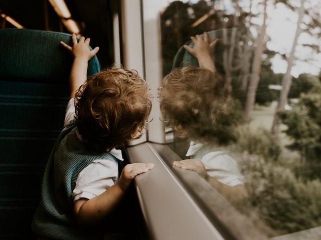 Malý chlapec pozerá z okna
